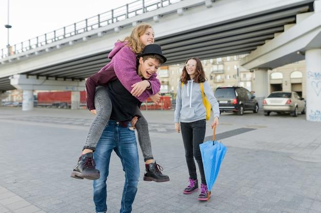 Tienerjongen en twee meisjes die en pret spreken openlucht hebben