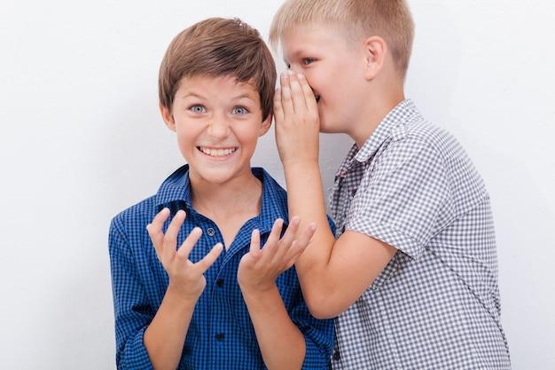 Tienerjongen, fluisteren, in, de, oor, een, geheim, om te, friendl, op wit, background