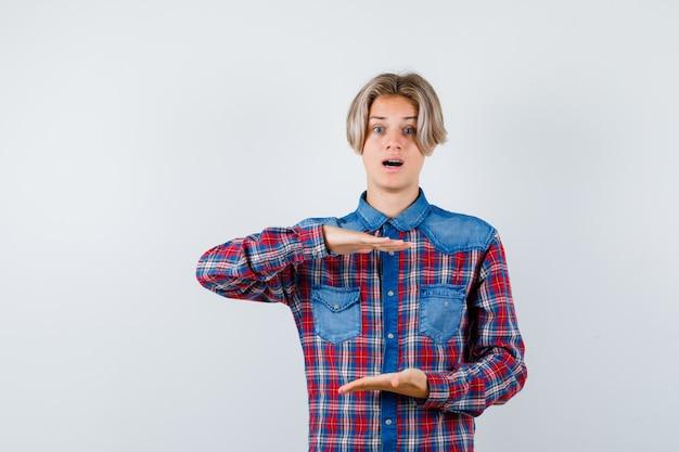 Tienerjongen in geruit overhemd die maatteken tonen en verbijsterd kijken, vooraanzicht.