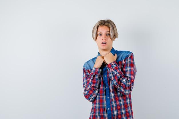 Tienerjongen in geruit overhemd die vuisten over borst houdt en angstig, vooraanzicht kijkt.