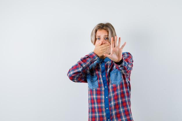 Tienerjongen in geruit overhemd met hand op mond terwijl hij stopgebaar toont en bang kijkt, vooraanzicht.