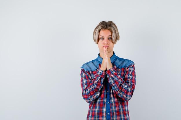 Tienerjongen in geruit overhemd met handen in biddend gebaar en hoopvol kijkend, vooraanzicht.