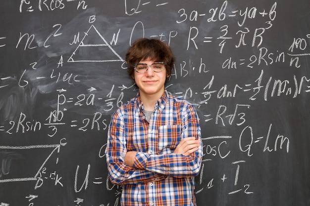 Tienerjongen in glazen, bord dat met wiskundige formules wordt gevuld