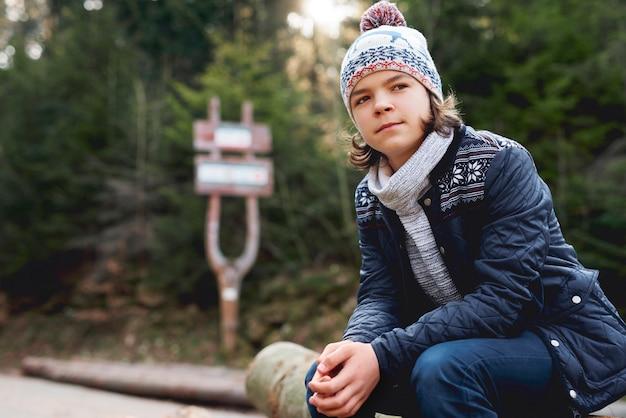 Tienerjongen in het herfstbos