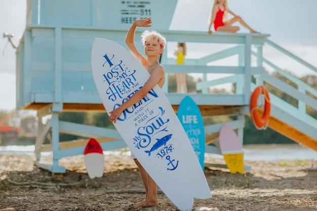 Tienerjongen in rode hoofdband poseren met witte surfplank met een citaat erop op het strand
