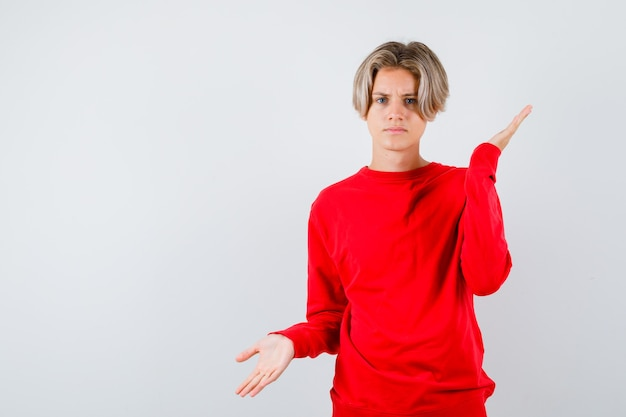 Tienerjongen in rode sweater die hulpeloos gebaar toont en onbeslist kijkt, vooraanzicht.