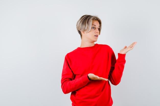 Tienerjongen in rode trui die doet alsof hij iets laat zien en verbijsterd kijkt, vooraanzicht.