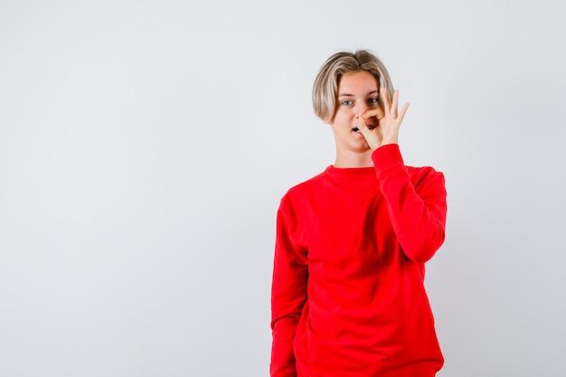 Tienerjongen in rode trui die een goed gebaar toont en er vrolijk uitziet, vooraanzicht.