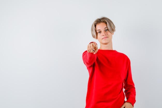 Tienerjongen in rode trui die naar voren wijst en er zelfverzekerd uitziet, vooraanzicht.