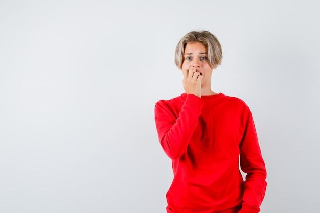 Tienerjongen in rode trui die nagels bijt en er bezorgd uitziet, vooraanzicht.