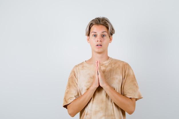 Tienerjongen in t-shirt die handen in gebedsgebaar houdt en verbaasd kijkt, vooraanzicht.