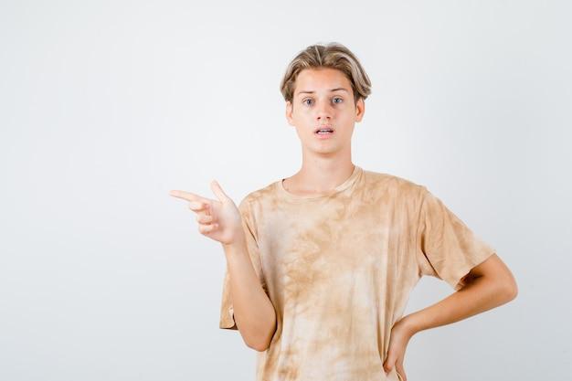 Tienerjongen in t-shirt die naar links wijst en teleurgesteld kijkt, vooraanzicht.