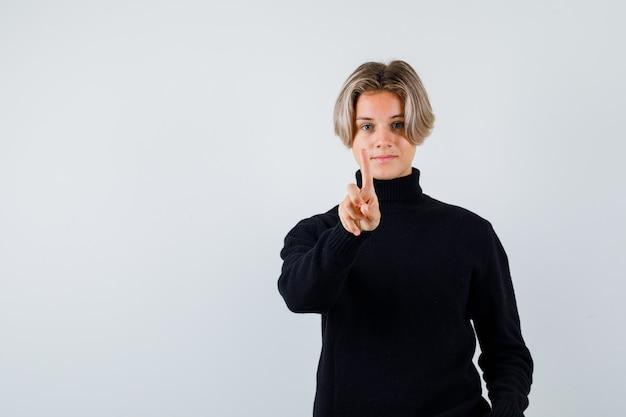 Tienerjongen in zwarte sweater die één vinger toont en vreedzaam, vooraanzicht kijkt.