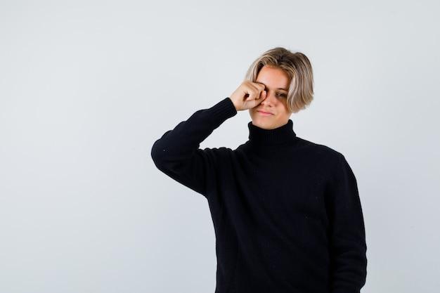 Tienerjongen in zwarte sweater die ogen met vuist wrijft en slaperig, vooraanzicht kijkt.