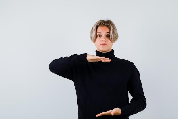 Tienerjongen in zwarte trui die doet alsof hij iets vasthoudt en er verbaasd uitziet, vooraanzicht.