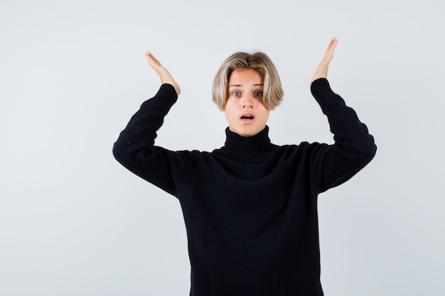 Tienerjongen in zwarte trui die handpalmen spreidt en geschokt kijkt, vooraanzicht.