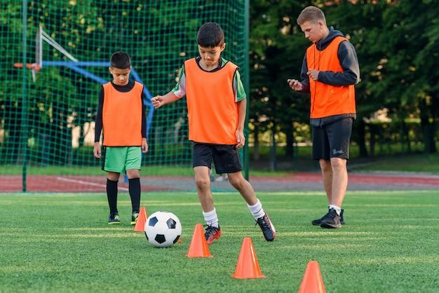 Tienerjongen leert de bal tussen trainingskegels te cirkelen in het voetbalstadion.