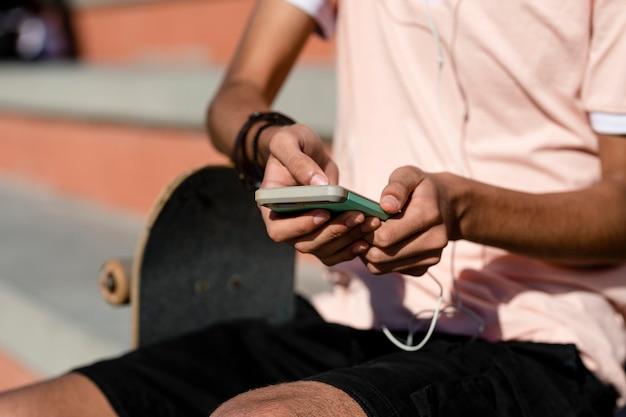 Tienerjongen luistert naar muziek in een skatepark in venice beach, los angeles
