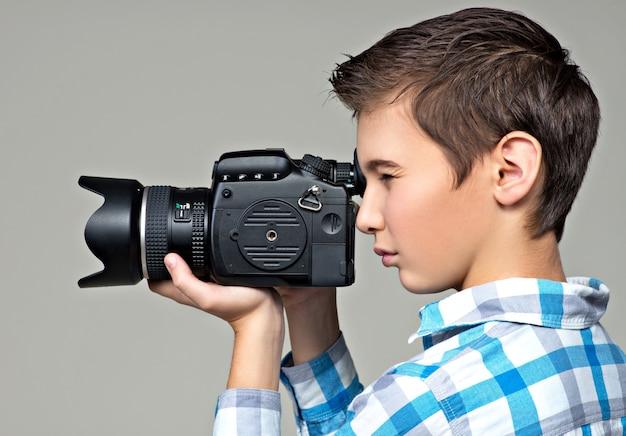 Tienerjongen met dslr-camera fotograferen. jongen met camera die foto's maakt. profiel portret.