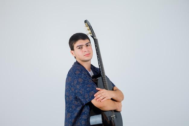Tienerjongen met gitaar op de borst in t-shirt en op zoek naar vertrouwen
