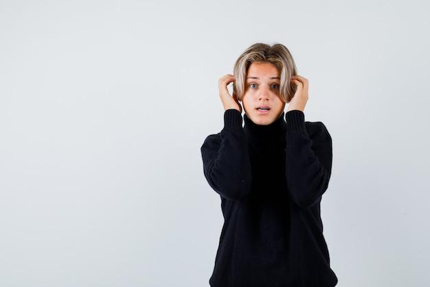 Tienerjongen met handen dichtbij gezicht in zwarte sweater en nadenkend, vooraanzicht.