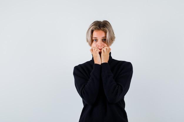 Tienerjongen met handen op mond in zwarte sweater en bang, vooraanzicht.