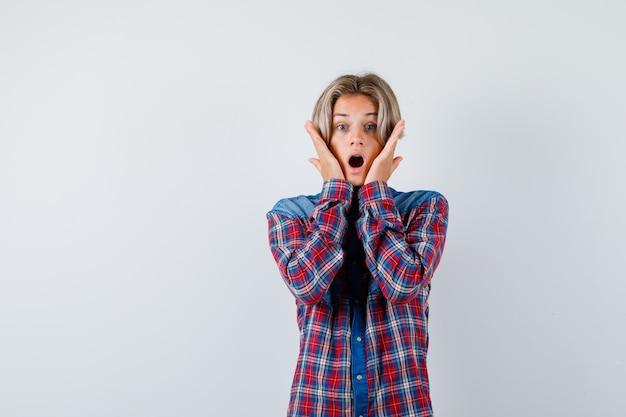Tienerjongen met handen op wangen in geruit overhemd en verbaasd, vooraanzicht.