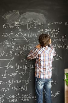 Tienerjongen met krijt die ingewikkelde wiskundige formules op zwarte raad schrijft