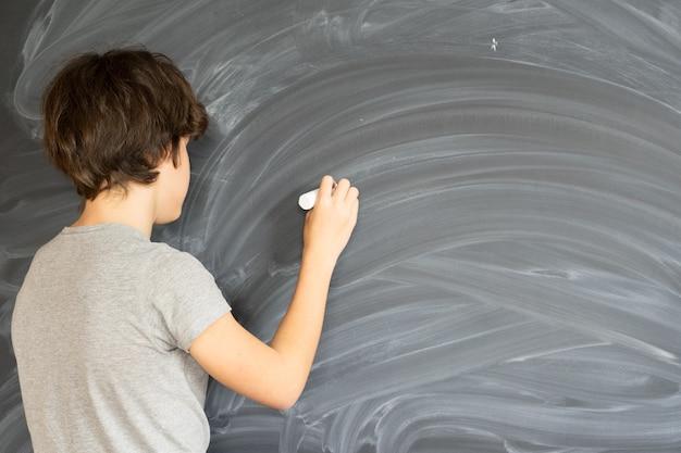 Tienerjongen met krijt in hand die op lege zwarte raad schrijft
