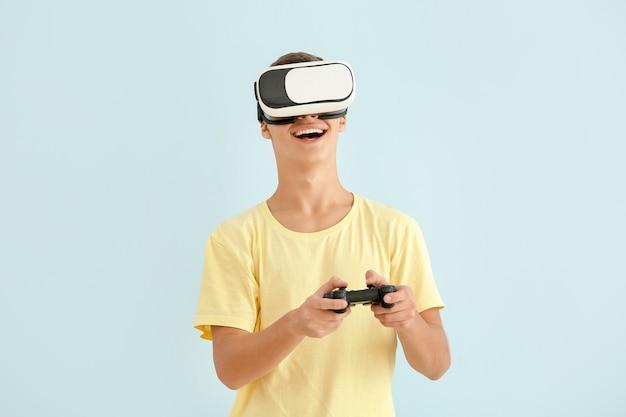 Tienerjongen met virtual reality-bril spelen van videospellen