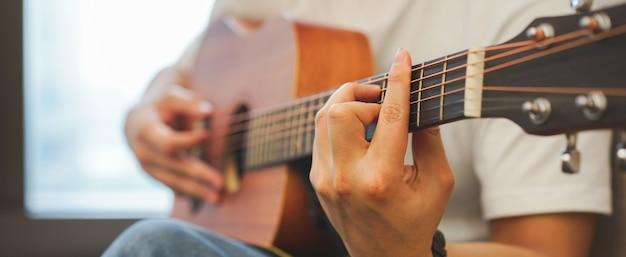 Tienerjongen open laptop voor zoeklied en klassieke gitaar spelen