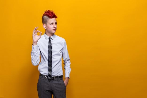 Tienerjongen over geïsoleerde gele muur die positief gebaar met ok handgebaar goedkeuren