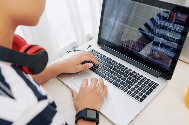 Tienerjongen programmeren op laptop