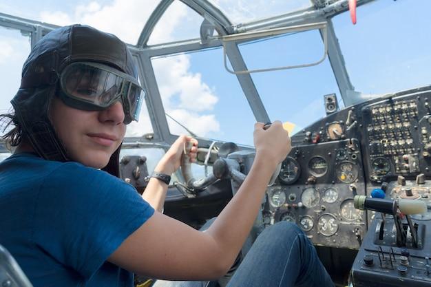 Tienerjongen retro piloot in antieke vintage vliegtuigcabine