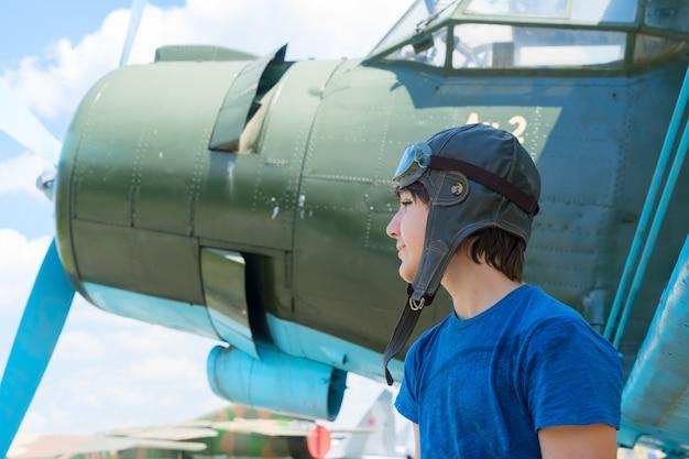 Tienerjongen retro piloot in helm en googles voor vintage vliegtuig