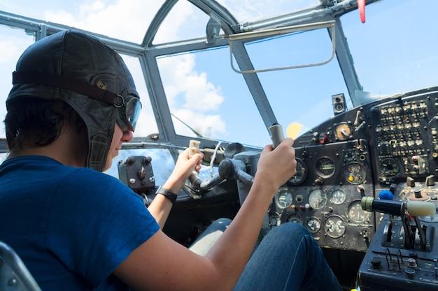 Tienerjongen retro piloot in vintage vliegtuigcabine