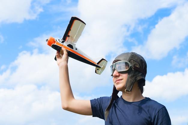 Tienerjongen retro piloot playnig met speelgoed vliegtuig