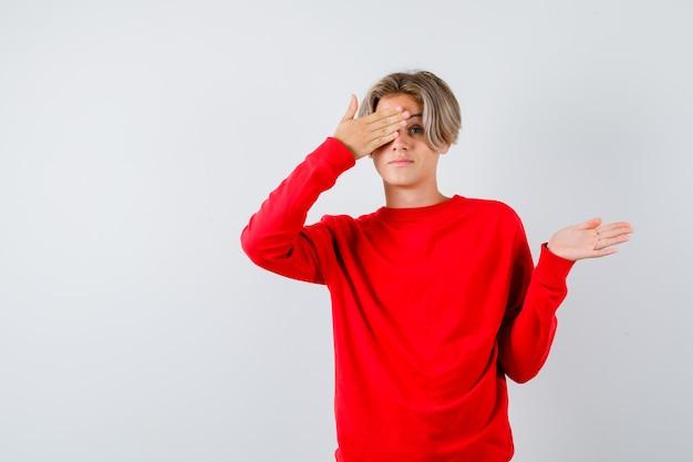 Tienerjongen sluit oog met hand, toont welkom gebaar in rode trui en ziet er bang uit, vooraanzicht.