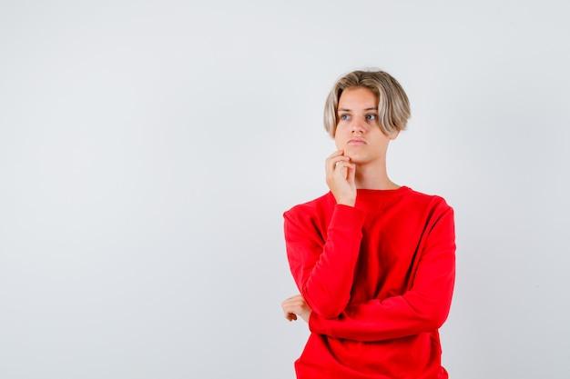 Tienerjongen staat in denkende pose in rode trui en kijkt gepreoccupeerd. vooraanzicht.