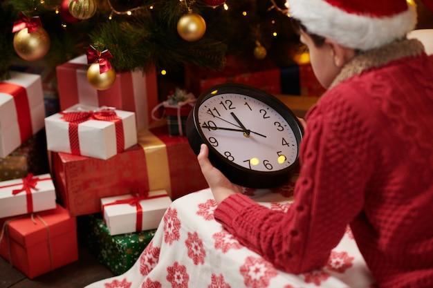 Tienerjongen wacht op de kerstman en kijkt naar de klok, liggend binnen in de buurt van versierde kerstboom met verlichting, verkleed als kerstman-helper - prettige kerstdagen en fijne feestdagen!