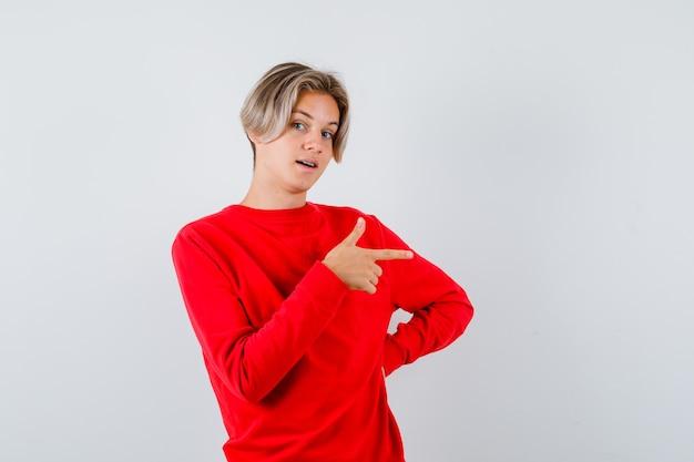 Tienerjongen wijst naar de rechterkant in rode trui en kijkt verrast. vooraanzicht.