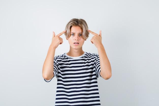 Tienerjongen wijzend naar zijn hoofd in t-shirt en verward kijken. vooraanzicht.