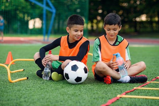 Tienerjongens in voetbaluniformen die rusten op het sportveld.
