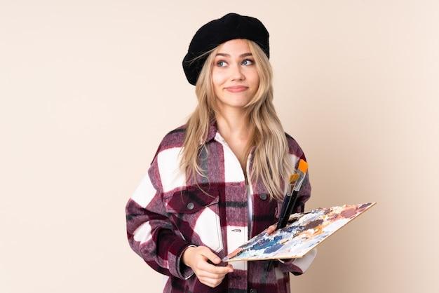 Tienerkunstenaarmeisje die een palet houden dat op blauwe muur wordt geïsoleerd die twijfelsgebaar maken die kant kijken