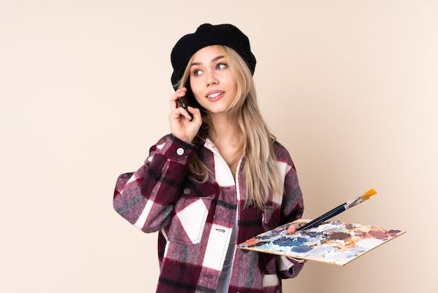 Tienerkunstenaarmeisje die een palet houden dat op blauwe te nemen holdingskoffie en mobiel wordt geïsoleerd
