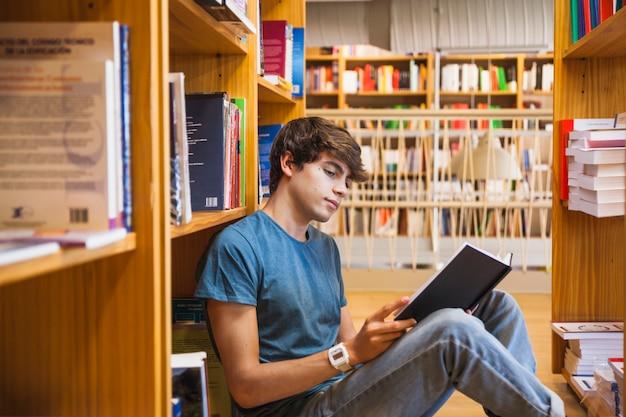Tienerlezing op vloer tussen boekenplanken