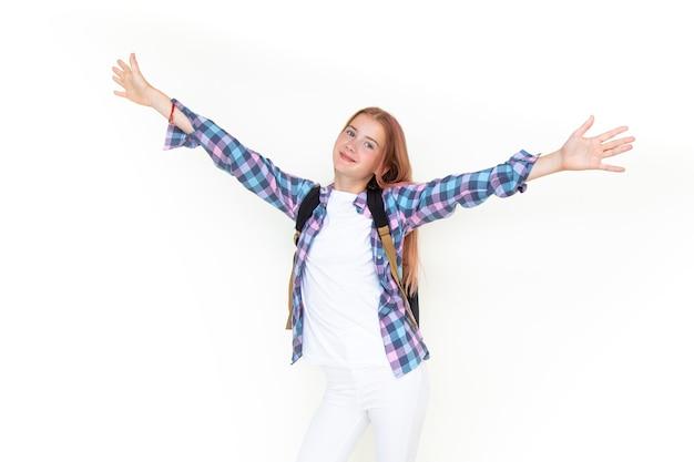 Tienermeisje 11 jaar oude schooljongen die naar de camera kijkt op een witte achtergrond met een rugzak en glimlachend haar handen hoog houdt. gekleed in een geruit overhemd