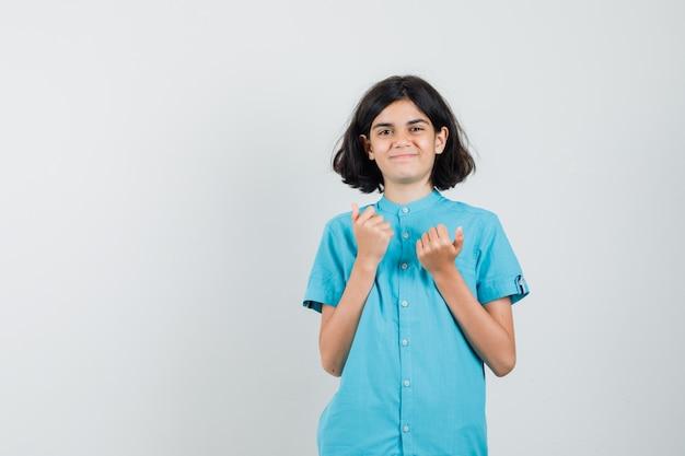 Tienermeisje aarzelt om duim in blauw overhemd te tonen en ziet er ingewikkeld uit