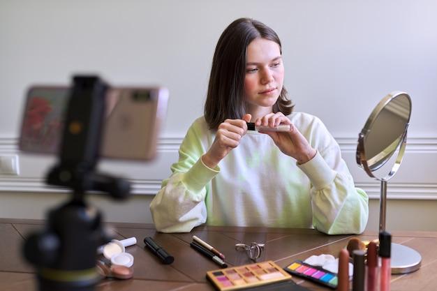 Tienermeisje, beautyblogger die video filmt voor kanaalblog, met lipgloss. make-up vertellen en laten zien die het gebruikt en onzichtbare natuurlijke make-up doet. schoonheid, technologie, communicatie tieners online