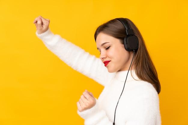 Tienermeisje bij gele muur het luisteren muziek en het dansen wordt geïsoleerd die
